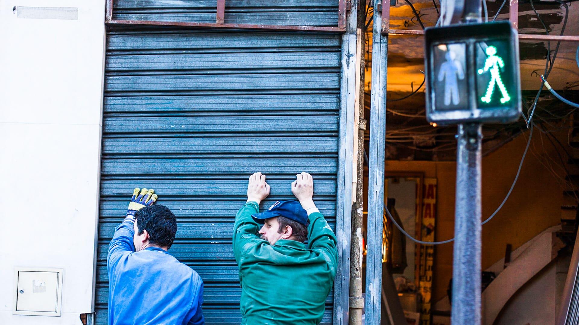Handwerker stützen defekten Rollladen