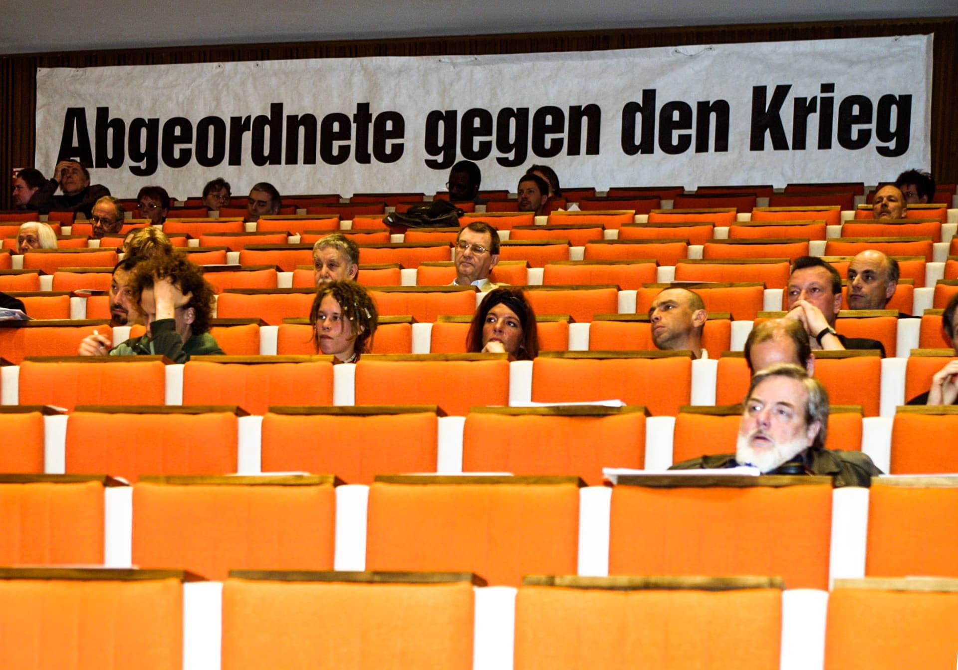 Weitgehend leere Sitze vor einem kriegskritischen Banner