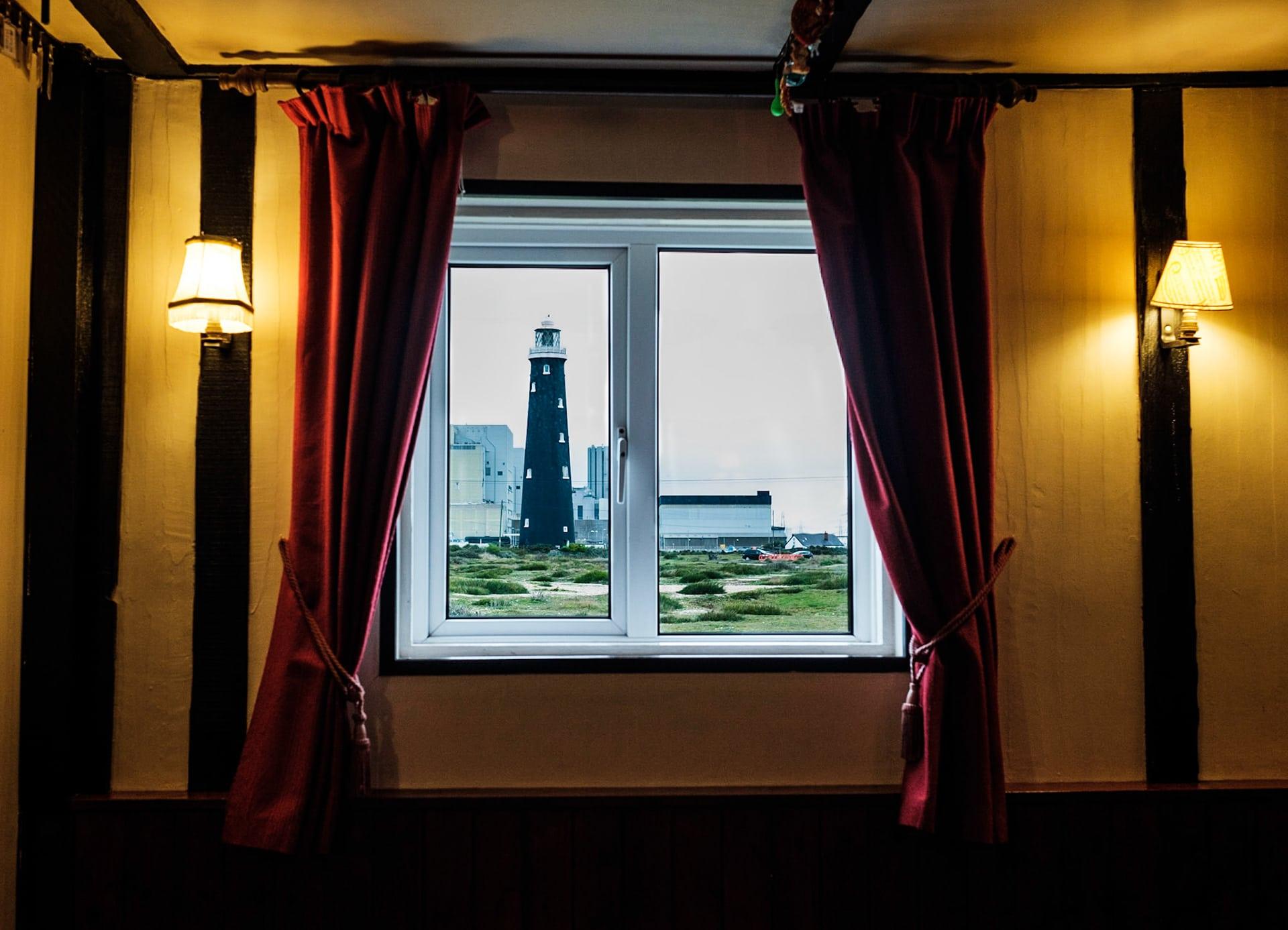 Blick aus doppelverglastem Kneipenfenster auf einen Leuchtturm